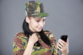 Happy woman soldier looks at a mobile phone — Stock Photo