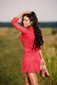 Beautiful brunette woman with shoes in hand on a field at sunset — Stock Photo