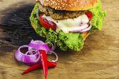Yummy Hamburger with Veggies on Wooden Table — Stock Photo