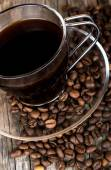 Glass cup of coffee with coffee beans on wood — Stock Photo