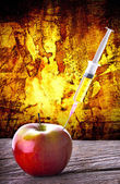 GMO syringe Injection into red apple dramatic abstract background — Stock Photo