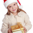 Pretty smiling little girl in Santa's red hat holding Christmas box — Stock Photo #60688331