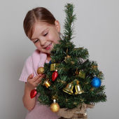 Smiling girl near a Christmas tree — Stock Photo