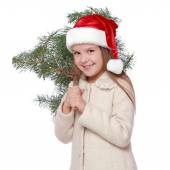 Positive young girl in Santa's hat is happy and laughing with Christmas tree — Photo