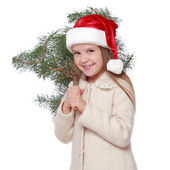Positive young girl in Santa's hat is happy and laughing with Christmas tree — Stockfoto