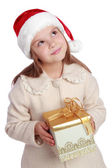Pretty smiling little girl in Santa's red hat holding Christmas box — 图库照片