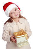 Pretty smiling little girl in Santa's red hat holding Christmas box — Photo