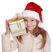 Pretty smiling little girl in Santa's red hat holding Christmas box — Stockfoto