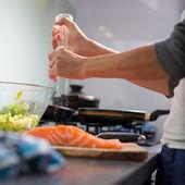 Woman seasoning a salomn filet — Stock Photo