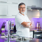 Senior man standing in his modern kitchen, — Stockfoto