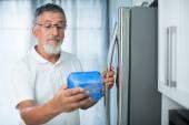 Senior man in his kitchen by the fridge — Stock Photo