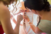 Bridesmaids helping bride lacing up dress — Stock Photo