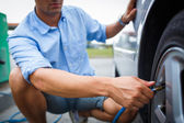 Driver checking air pressure and filling air in the tires — Stock Photo