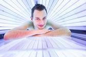 Uomo che si distende durante una seduta abbronzante — Foto Stock