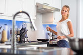 Woman in her modern, clean and bright kitchen — Stok fotoğraf