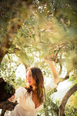 Brunette woman on the beach, amid olive trees — Stock Photo