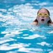 Girl in goggles and cap swimming breast stroke — Stock Photo #61563943