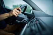 Male driver's hands driving a car on a highway — Stock Photo