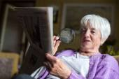 Senior woman reading morning newspaper — Stock Photo