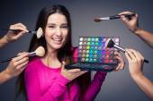 Cute make-up artist holding her vast palette of colors — Stock Photo