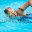 Girl in goggles and cap swimming crawl stroke — Stock Photo #63725991