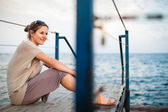 Woman on a jetty at the seacoast — Stock Photo