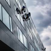 Climbers washing windows of high-rise building — Stock Photo