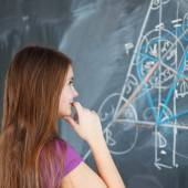 Young college student writing on the blackboard — Stock Photo