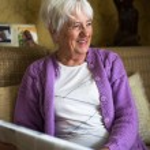 Senior woman reading morning newspaper — Stock Photo #69974359