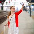 Woman at a train station - taking a selfie — Stock Photo #69974829