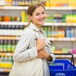 Woman with a shopping basket buying groceries in a — Stock Photo #73295255