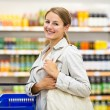 Woman with a shopping basket buying groceries in a — Stock Photo #73295261