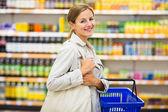 Woman with a shopping basket buying groceries in a — Stock Photo