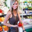 Beautiful young woman shopping for fruits and vegetables — Stock Photo #76322847