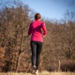 Young woman running outdoors on a lovely sunny winter/fall day — Stock Photo #79676256