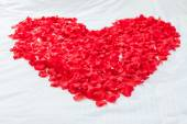 Heart made with flowers on honeymoon bed — ストック写真