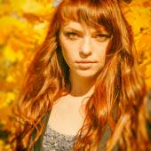 Beautiful woman with freckle and red hair in autumn park — Stock Photo
