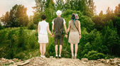 Young active guy and girls hipsters hold hands over an abyss — Stock Photo