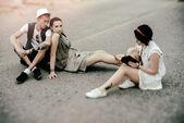 Jovens descolados de homem e mulheres tem um descanso na estrada — Fotografia Stock
