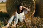 Beautiful girl hipster looks distance against hay bale in fall — Stock Photo