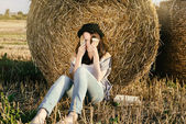 Girl hipster confusedly covers face against hay bale — Stock Photo
