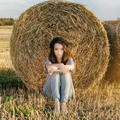 Beautiful girl hipster against hay bale in fall — Stock Photo