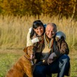 Cheerful couple with dog in autumn park — Stock Photo #53530075