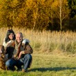 Cheerful couple with dog in autumn countryside — Stock Photo #53530079