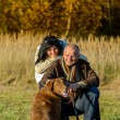 Cheerful couple with dog in autumn countryside — Stock Photo #53530081
