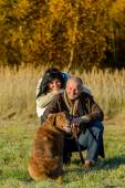 Cheerful couple with dog in autumn countryside — Foto Stock