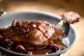 Roasted duck leg in red wine cherry sauce — Stock Photo