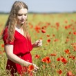 Woman at red dress with scarlet poppy — Stock Photo #51970073