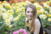 Woman and many yellow roses around her — Stock Photo