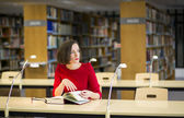 Woman in thought in library looking left — Stock Photo